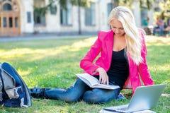 Começo do ano escolar O menina-estudante bonito lê livros Imagem de Stock