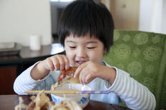 Comer asiático bonito pequeno da menina foto de stock royalty free