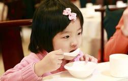 Comer asiático pequeno da menina Foto de Stock Royalty Free