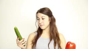Comer bonito da jovem mulher vegetais guardando o pepino e a pimenta vermelha alimento saudável - conceito de corpo saudável vídeos de arquivo