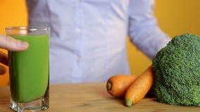 Comer saudável, alimento do vegetariano, dieta e conceito da desintoxicação - mão da mulher que põe o vidro do suco de cenoura so filme