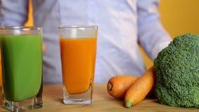 Comer saudável, alimento do vegetariano, dieta e conceito da desintoxicação - mão da mulher que põe o vidro do suco de cenoura so video estoque