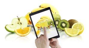 Comer saudável do alimento e conceito da dieta equilibrada, mão que aponta o vidro do suco na tela digital da tabuleta com fundo  foto de stock royalty free