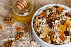 Comer saudável Na placa de madeira é o muesli, mel em um frasco, foto de stock
