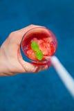 Comer un jugo de fruta fresco por la piscina Fotos de archivo