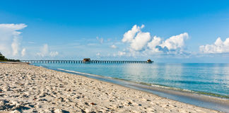 Comercial pier on the tropical west coast of Florida. With a sandy beach on the Gulf of Mexico in late morning Royalty Free Stock Photos