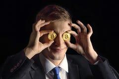 Comerciante atractivo divertido joven feliz del hombre de negocios que sostiene cryptocurrency del bitcoin en vez de ojos, en neg foto de archivo libre de regalías