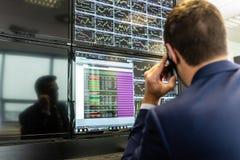 Comerciante común que mira datos del mercado sobre las pantallas de ordenador Fotos de archivo libres de regalías