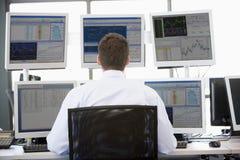 Comerciante común que mira monitores múltiples Imágenes de archivo libres de regalías