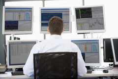 Comerciante conservado em estoque que olha monitores múltiplos