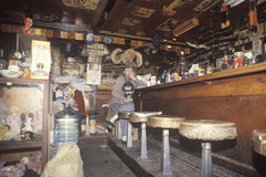 Comerciante da mulher que senta-se no tamborete de barra na loja da sucata, Los Angeles, Califórnia imagens de stock royalty free