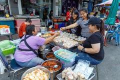 Comerciante de sexo femenino de la sonrisa en las compras del mercado de la comida de la calle en Nonthaburi imagenes de archivo