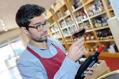 Comerciante de vino que sostiene la botella y el vino rojo de cristal imagenes de archivo