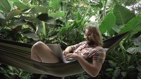 Comerciante del ryptocurrency del ¡de Ð que hace negocio en el ordenador portátil mientras que miente en la hamaca metrajes