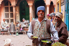 Comerciante do alimento da rua que faz um prato para clientes com fome pobres da cidade velha Varanasi Imagens de Stock Royalty Free
