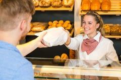 Comerciante en el bolso de la panadería de pan al cliente foto de archivo