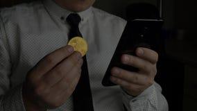 Comerciante en la camisa blanca con el lazo usando smartphone negro y moneda de oro disponible del bitcoin BTC de los controles metrajes