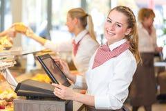 Comerciante en la panadería que trabaja en la caja registradora foto de archivo libre de regalías