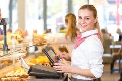 Comerciante en la panadería que trabaja en la caja registradora fotos de archivo libres de regalías
