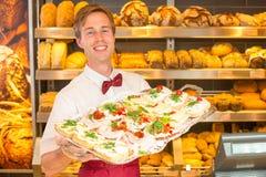 Comerciante en la tienda del panadero con la bandeja de bocadillos Foto de archivo libre de regalías