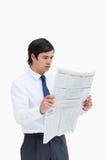 Comerciante joven que lee las noticias Imagen de archivo libre de regalías
