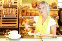 Comerciante na loja do padeiro que prepara o café e o bolo Foto de Stock