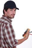 Comerciante que sostiene un multímetro fotos de archivo