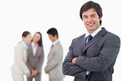 Comerciante sonriente con los brazos doblados y colegas detrás de él Imagen de archivo libre de regalías