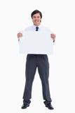 Comerciante sonriente que lleva a cabo la muestra en blanco Fotos de archivo