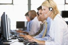 Comerciantes conservados em estoque com os auriculares no trabalho Imagens de Stock Royalty Free