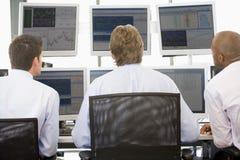 Comerciantes conservados em estoque que vêem monitores Imagem de Stock