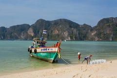 Comerciantes da água potável que vêm pelo barco de madeira à vila tropical Fotos de Stock