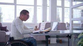 Comercio electrónico del hombre discapacitado perjudicado, acertado con gafas en trabajos de la silla de ruedas sobre el ordenado almacen de metraje de vídeo