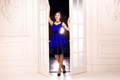 She Comes. Girl in blue dress open white doors and enter indoor from the dark . stock image