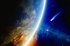 Comet approaches Earth. Abstract scientific background - comet approaches glowing planet Earth, nebula and stars in space. Elements of this image furnished by stock photography