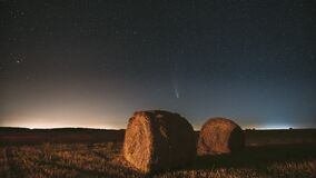 Comet Neowise C/2020 F3 In Night Starry Sky Above Haystacks In Summer Agricultural Field. Night Stars Above Rural