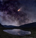 Comet over mountain lake. Night landscape with mountain lake and bright comet reflected in it Stock Photo