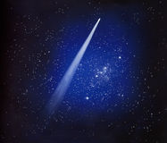 Comet Among the Stars. Comet streaks through the night sky leaving a long tail in its path Stock Images