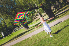 Cometa del arco iris en el cielo muchacha del multirace que juega y que corre con la cometa imagen de archivo libre de regalías