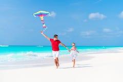 Cometa del vuelo de la familia junto en la playa blanca tropical imagen de archivo libre de regalías
