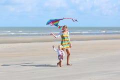 Cometa del vuelo de la madre y del niño en la playa fotos de archivo libres de regalías