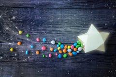 Cometa, píldoras multicoloras dulces del caramelo de la estrella el caer en el regalo de papel imagen de archivo libre de regalías