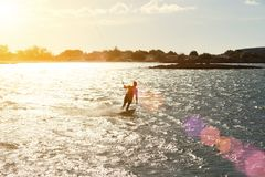 Cometa que practica surf en la puesta del sol Imagen de archivo