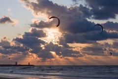 Cometa que practica surf en la puesta del sol en la playa Foto de archivo
