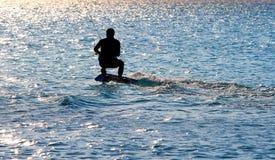 Cometa que practica surf en la puesta del sol Silouette de la persona que practica surf de la cometa Imagen de archivo libre de regalías