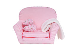 Comfi pink armchair with pillows, blanket on it. Tiny pink armchair with pillows and white blanket isolated on white background Royalty Free Stock Image