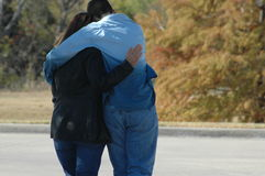 Comfort. Son hugging his mom as they walk. Two people walking holding each other stock photos