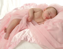 Comfort. Sleeping baby reclining on pink covers Stock Image
