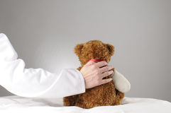 Comfort. An injured teddy getting comfort by a doctor royalty free stock images