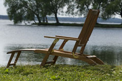 Comfort in an armchair. A deckchair on lakeside on green grass Royalty Free Stock Photo